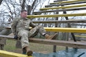 Spc. Tanner Rider, Texas Army National Guard, works his way over and under the wooden beams during the obstacle course portion of the Texas National Guard's 2019 Best Warrior Competition at Camp Swift Feb. 28, 2019. Over the span of 24 hours, the competitors have been put through an obstacle course, nighttime navigation, a 12-mile ruck march wearing a 35-pound ruck sack and performing a modified Army physical fitness test which consisted of pushups, sit-ups, and a four-mile run. (Texas Air National Guard photo by Senior Airman Bryan Swink)
