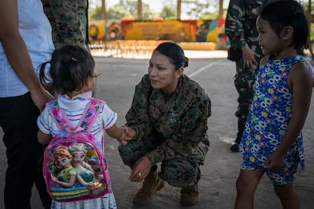 .S. Navy Religious Program Specialist 2nd Class Nancy Guillermo meets a local girl before a community relations event in support of Exercise Balikatan at Calangitan Elementary School in Capas, Tarlac, Philippines, April 23, 2018.