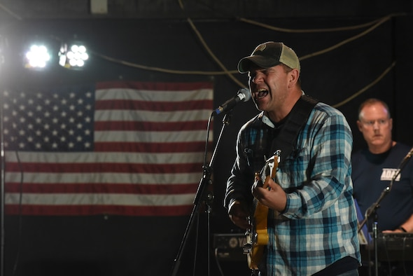Air Forces Central Command band member Staff Sgt. Ryan Manzi sings a song for the crowd of deployed members at Al Dhafra Air Base, United Arab Emirates, Mar. 20, 2019.