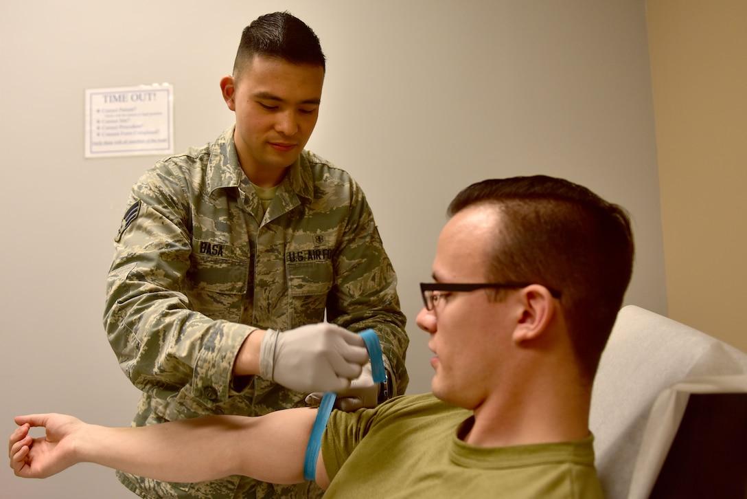 A man wearing the Airman Battle Uniform ties a blue ribbon around a mans arm.