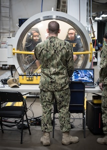 PANAMA CITY, Florida – Research Physiologist Lt. Travis Doggett, center, directs aircrew via radio during simulated flight in the Fluctuating Altitude Simulation Technology (FAST) system Jan. 14, 2019 at Navy Experimental Diving Unit. The system was developed and built by Naval Surface Warfare Center Panama City Division.