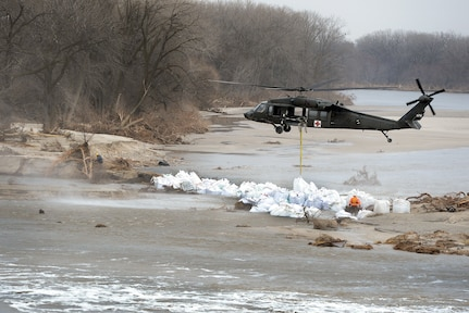 An aircrew with the Nebraska Army National Guard's 2nd Battalion, 104th Aviation Regiment, uses a UH-60 Black Hawk helicopter to lower 1,500-pound sandbags into place to stem flooding from a breached levee along the Loup River, Nebraska. More than 340 Guard members have responded to flooding in Nebraska, Missouri, Iowa and other Midwest states.
