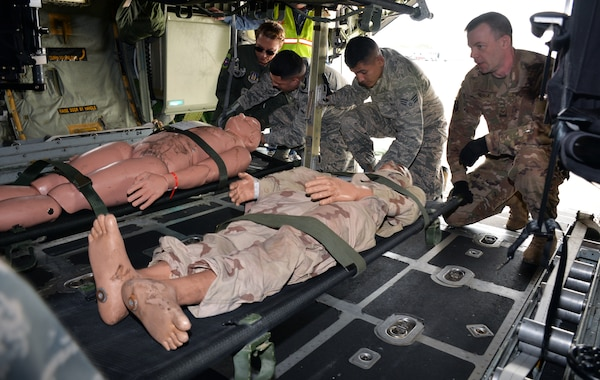 59th Medical Wing and 433rd Aeromedical Evacuation Squadron personnel load simulated patients into litter stanchions in a C-130H Hercules during a National Disaster Medical System exercise at Joint Base San Antonio-Lackland March 20.