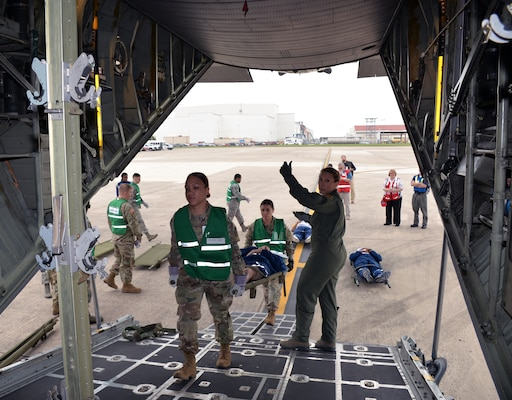 Air Force Maj. Carolyn Stateczny (right), 433rd Aeromedical Evacuation Squadron flight nurse, guides Spcs. Sandessa Jones and Maryssa Alfonso, Brooke Army Medical Center, into a C-130H Hercules aircraft to load a simulated litter patient for air transport at Joint Base San Antonio-Lackland March 20. Several military and civilian organizations participated in a National Disaster Medical System exercise