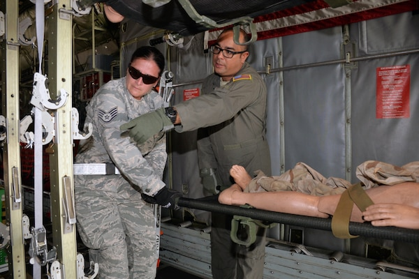 Staff Sgt. Jennifer Melanson, 559th Aerospace Medicine Squadron, and Chief Master Sgt. Jeremy Morton, 433rd Aeromedical Evacuation Squadron, load a simulated litter patient into a litter stanchion in a C-130H Hercules during a National Disaster Medical System exercise at Joint Base San Antonio-Lackland March 20.