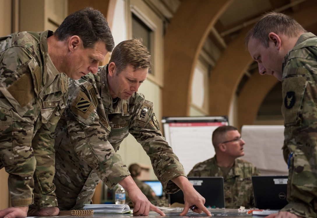 Lt. Col. Matthew Emerson, director of operations for the 146th Air Support Operations Squadron (146th ASOS), Oklahoma Air National Guard, discusses grid coordinates on a map with Maj. Bradley Wallace, brigade fire support officer for the Army National Guard Armored Brigade Combat Team, 34th Infantry Division (1/34th ABCT), and Capt. Trevor Smith, operations flight commander for the 146th ASOS, during the brigade's 19-05 Command Post Exercise (CPX) March 8-9, 2019, at Camp Ripley in Little Falls, Minn. The CPX was a practice virtual battle exercise for the brigade to practice their battle drills, and the 146th ASOS will continue partnering with the 1/34th ABCT later in the year to assist in a graded warfighter exercise, as well as other trainings next year. (U.S. Air National Guard photo by Staff Sgt. Brigette Waltermire)