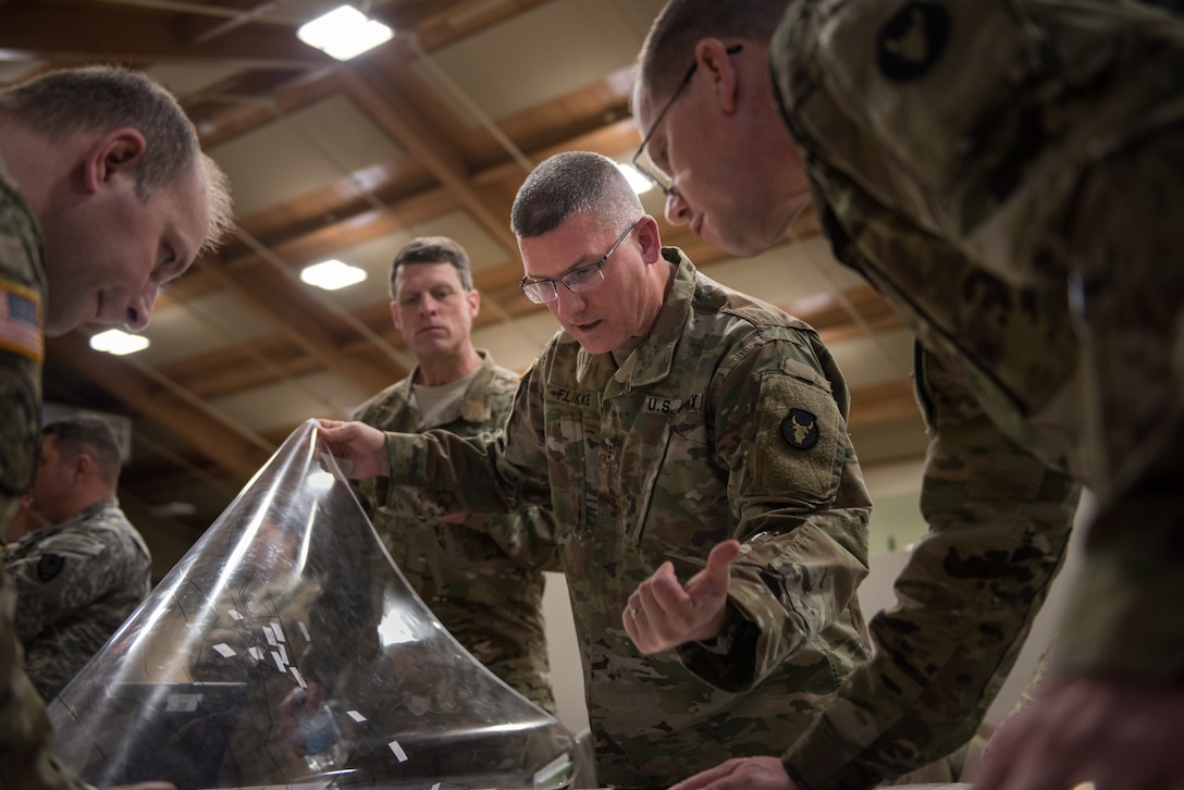 Chief Warrant Officer 3 Jonathan Flikke, brigade targeting officer for the Minnesota Army National Guard Armored Brigade Combat Team, 34th Infantry Division (1/34th ABCT), lifts a clear cover to a map during a discussion of troop positions in a simulated attack during the 19-05 Command Post Exercise (CPX) for the 1/34th ABCT, March 8-9, 2019, at Camp Ripley in Little Falls, Minn. The CPX was a practice virtual battle exercise for the brigade to practice their battle drills, and the 146th ASOS will continue partnering with the 1/34th ABCT later in the year to assist in a graded warfighter exercise, as well as other trainings next year. (U.S. Air National Guard photo by Staff Sgt. Brigette Waltermire)
