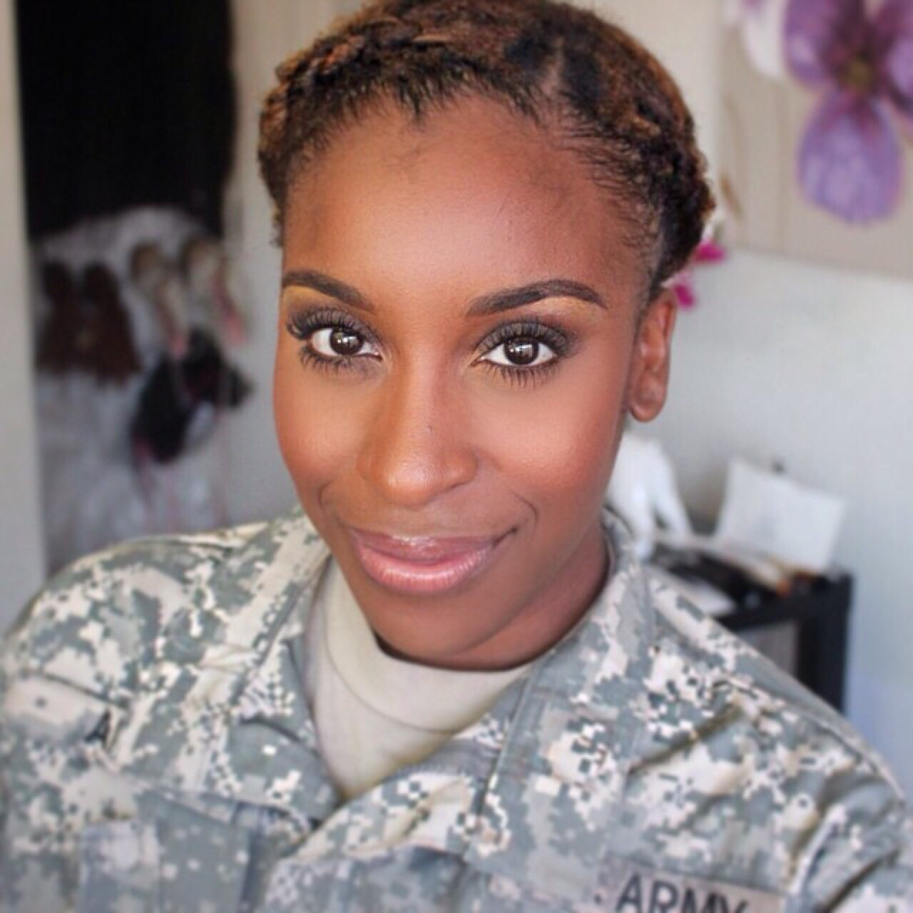 Female soldier in camouflage uniform poses for a selfie.