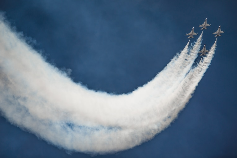 Four military jets soar across blue sky leaving white trails behind them.