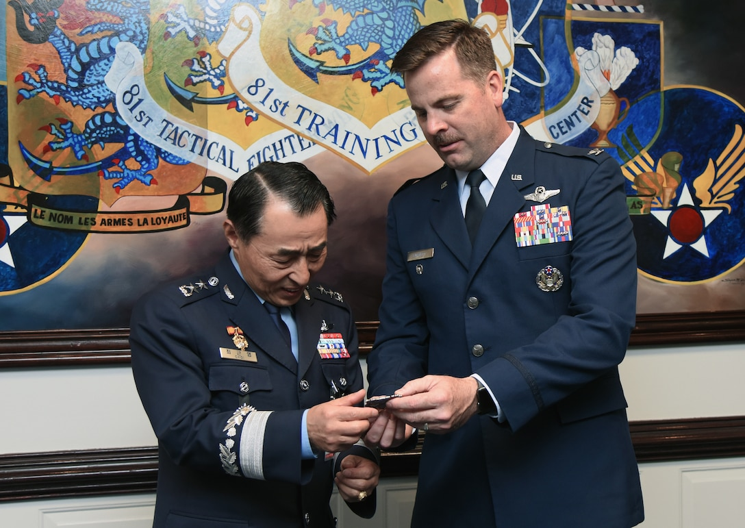 U.S. Air Force Col. Lance Burnett, 81st Training Wing vice commander, presents a coin to Republic of Korea Air Force Maj. Gen. Geunyoung Choi, ROKAF Air Education and Training Command commander, following an 81st TRW mission brief at the headquarters building on Keesler Air Force Base, Mississippi, March 22, 2019. Choi visited Keesler to help better develop ROKAF technical education through visiting U.S. Air Force future technology education sites.  (U.S. Air Force photo by Kemberly Groue)