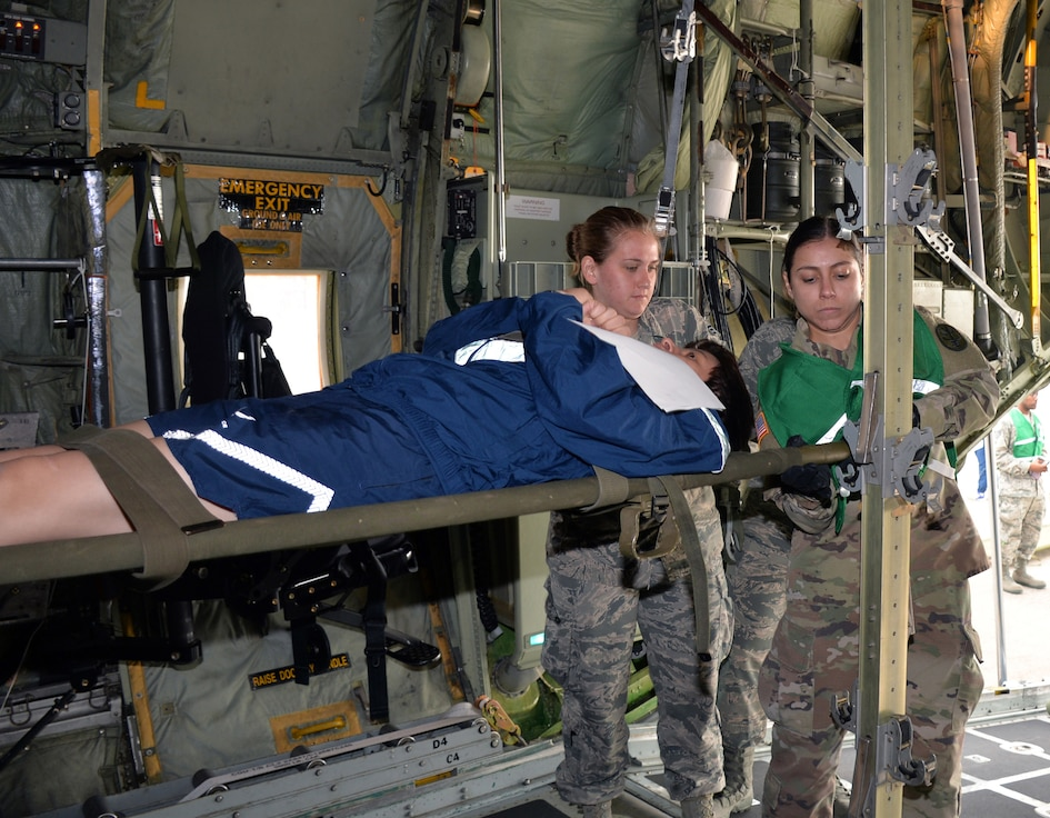Senior Airman Amanda Geffert, 433rd Aeromedical Evacuation Squadron flight medic, and Army Spc. Maryssa Alfonso, BAMC Alpha Company load a simulated litter patient into a C-130H Hercules aircraft to for air transport at Joint Base San Antonio-Lackland, Texas March 20, 2019.