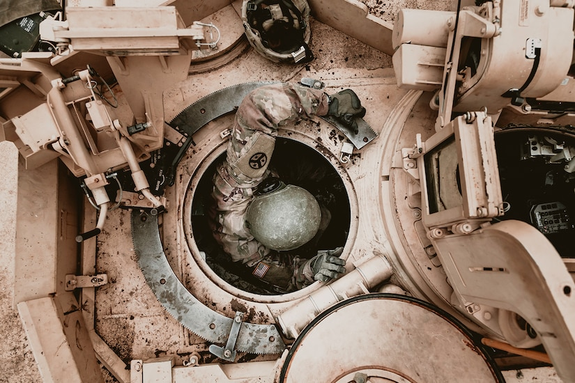 A soldier, shown from overhead, emerges from the top opening of a tank.