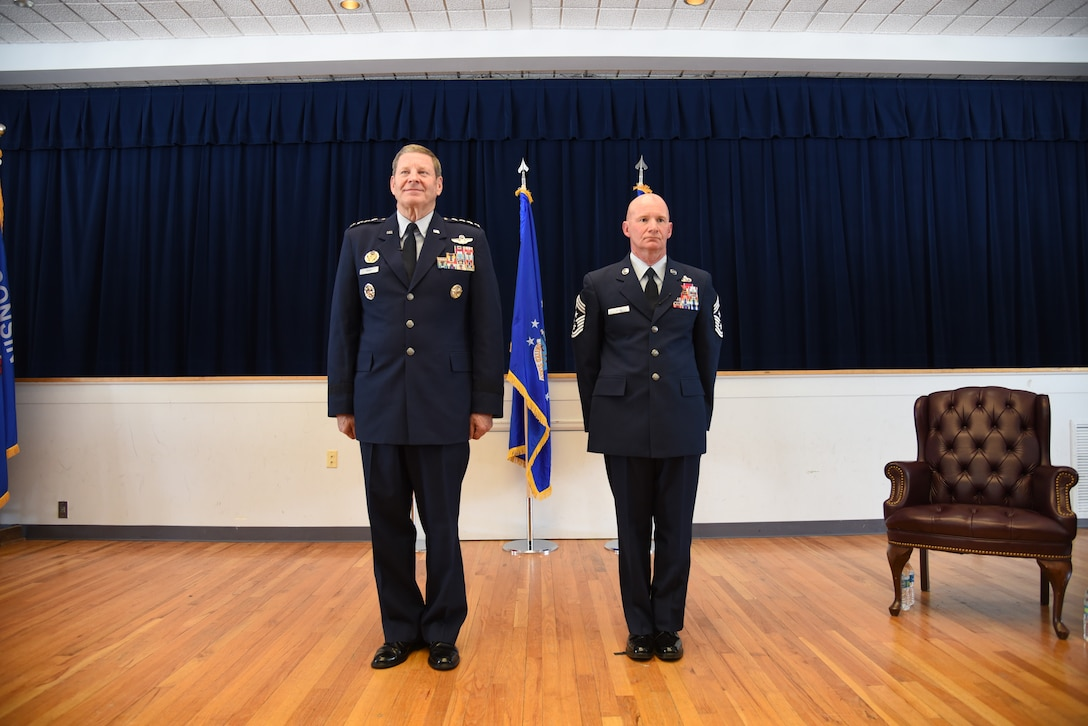 Retired Gen. Robin Rand and Chief Master Sgt. Thomas F. Good, 20th Air Force command chief, stand at attention during Chief Good's retirement ceremony March 5, 2019, at F. E. Warren Air Force Base. Chief Good retired as the 20th Air Force command chief in the presence of his wife, children and friends. (U.S. Air Force photo by Senior Airman Nicole Reed)