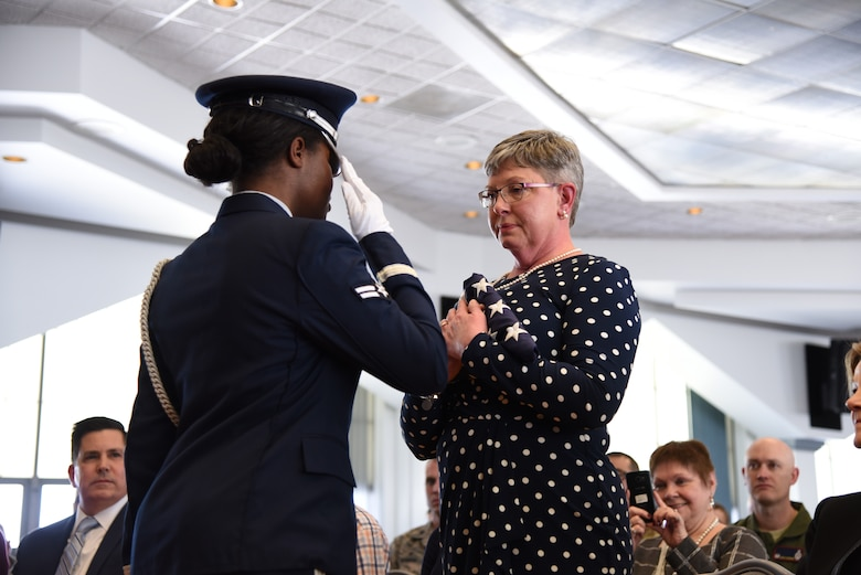A 90th Missile Wing honor guard member presents the American flag to Tennie Good during her husband's retirement ceremony March 5, 2019, at F. E. Warren Air Force Base, Wyo. Chief Master Sgt. Thomas F. Good, 20th Air Force command chief, retired as the 20th Air Force command chief in the presence of his wife, children and friends. (U.S. Air Force photo by Senior Airman Nicole Reed)