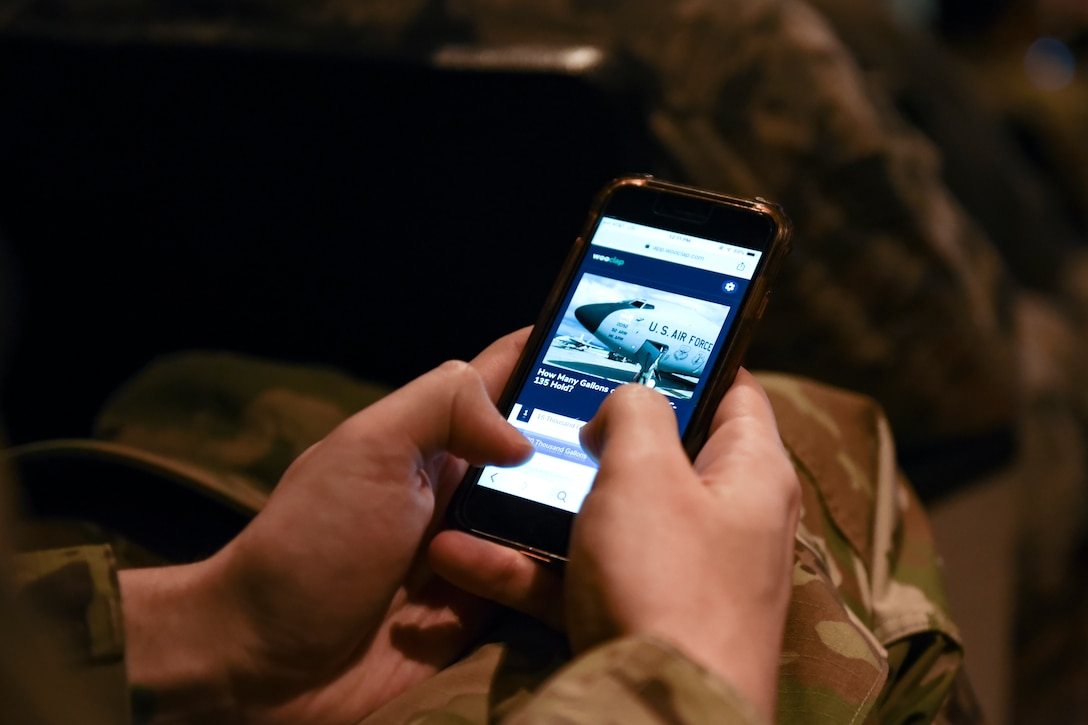 "A Team Fairchild airman uses an interactive poll app during a ""State of the Wing"" all-call at Fairchild Air Force Base, Washington, March 20, 2019. Salmi connected with Airmen through a real-time question and answer application, polling attendees and addressing concerns via the smart-phone app. (U.S. Air Force photo by Airman 1st Class Whitney Laine)"