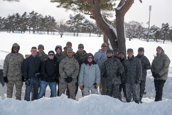 """U.S. Air Force Airmen with the 35th Civil Engineer Squadron emergency management flight and Japan Air Self-Defense Force members pause for a photo during the inaugural """"Snowblast"""" event at Misawa Air Base, Japan, Feb. 14, 2019. The emergency flight gathered for a snowball fight and capture the flag events with members of JASDF. This event provided an opportunity for Airmen to bond with their host-nation counterparts. (U.S. Air Force photo by 1st Lt. Jeremy Garcia)."""
