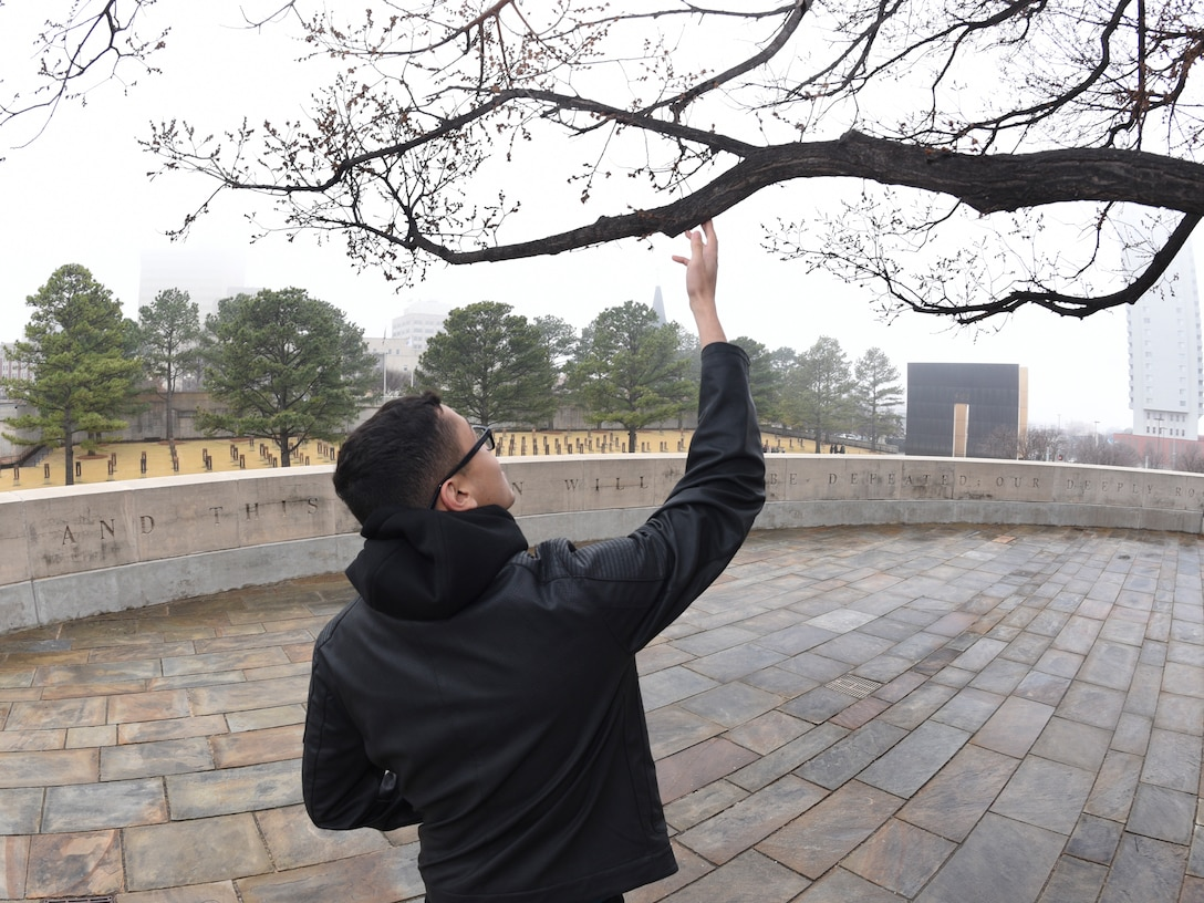 Airman 1st Class Willblas Coriano-Cotto, 552nd Operations Support Squadron intelligence analyst, looks at the giant 'survivor tree' at the Oklahoma City National Memorial Museum, site of the Alfred P. Murrah Federal Building bombing while attending Tinker Air Force Base's First Term Airmen Center downtown tour on March 8, 2019, Oklahoma City, Oklahoma.