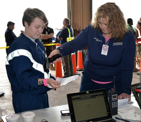 Chillon Montgomery (left), Methodist Healthcare, scans 343rd Training Squadron student Airman Bonnie Gunn's wristband March 20 at Joint Base San Antonio-Lackland. Montgomery and Gunn were participating in a National Disaster Medical System exercise, which involved multiple military and civilian agencies.
