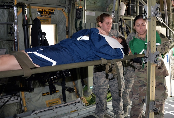 Senior Airman Amanda Geffert, 433rd Aeromedical Evacuation Squadron flight medic, and Army Spc. Maryssa Alfonso, BAMC Alpha Company load a simulated litter patient into a C-130H Hercules aircraft to for air transport at Joint Base San Antonio-Lackland March 20. Several military and civilian organizations participated in a National Disaster Medical System exercise.