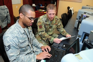 Two uniformed men look at a computer.
