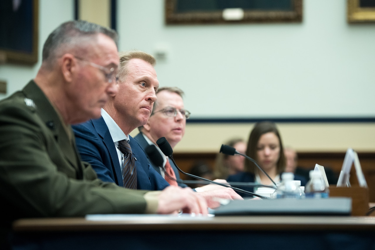 Two men speak before the House Armed Services Committee.