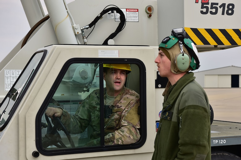 A man in the operational camouflage uniform in a crane speaks to a man in a flight suit and a headset.