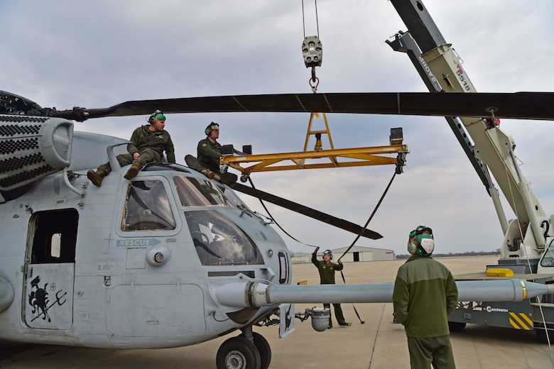 Men wearing a flight suit prepare to put a rotor blade from a CH-53E Super Stallion onto a crane.
