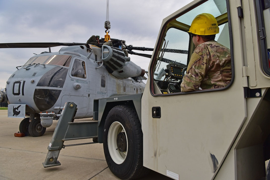 A man wearing the operational camouflage pattern uniform sits in a crane in front of a CH-53E Super Stallion.