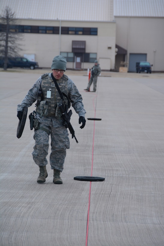Senior Airman Steven Hill, 507th Security Forces Squadron, places stanchion bases along a perimeter of rope securing aircraft on the flightline during an exercise geared toward wartime preparation and readiness March 2, 2019, at Tinker Air Force Base, Oklahoma. The 507th Air Refueling Wing's unit effectiveness inspection capstone event is scheduled for Nov. 15-19, 2019. (U.S. Air Force photo by Tech. Sgt. Lauren Gleason) (This photo has been altered for security purposes by blurring out identification badges.)