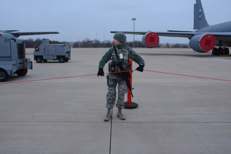 Senior Airman Taylor Adamson, 507th Security Forces Squadron, ropes off a secure perimeter around the aircraft on the flightline during an aircraft generation exercise geared toward wartime preparation and readiness March 2, 2019, at Tinker Air Force Base, Oklahoma. The 507th Air Refueling Wing's unit effectiveness inspection capstone event is scheduled for Nov. 15-19, 2019. (U.S. Air Force photo by Tech. Sgt. Lauren Gleason) (This photo has been altered for security purposes by blurring out identification badges.)