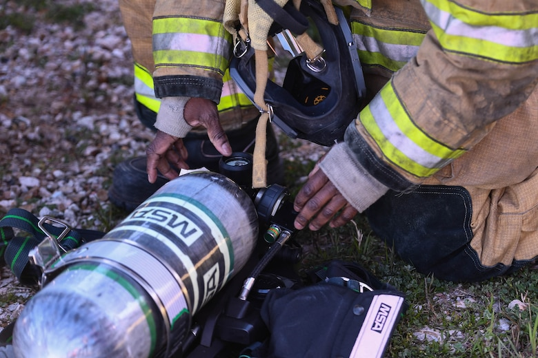 A Shreveport Fire Department firefighter checks over his gear before a live fire training exercise March 21, 2019, at Barksdale Air Force Base, Louisiana. Shreveport Fire Department conducts simulated aircraft fires every year with the 2nd Civil Engineering Squadron Fire Department. (U.S. Air Force photo by Airman Jacob B. Wrightsman)