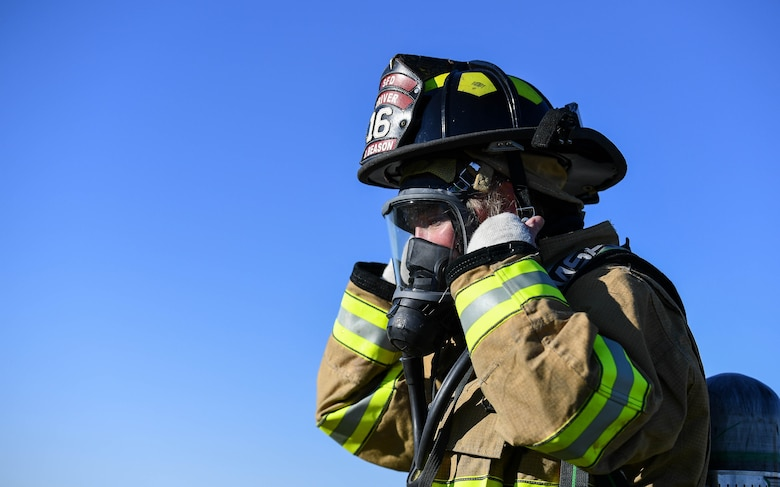 A Shreveport Fire Department firefighter adjusts her headgear during a live fire training exercise March 21, 2019, at Barksdale Air Force Base, Louisiana. Shreveport Fire Department conducts annual live fire training to complete their Federal Aviation Administration required training. (U.S. Air Force photo by Airman Jacob B. Wrightsman)