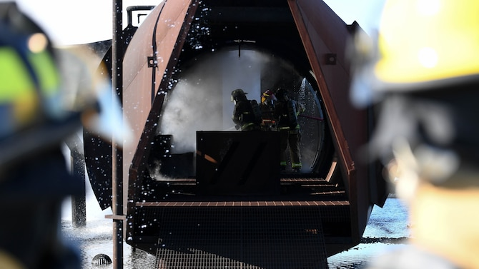 U.S. Air Force firefighters from the 2nd Civil Engineering Squadron and firefighters from the Shreveport Fire Department put out a fire during a live fire training exercise March 21, 2019, at Barksdale Air Force Base, Louisiana. The interior of the training aircraft is designed to test firefighters with simulated cargo and cockpit fires. (U.S. Air Force photo by Airman Jacob B. Wrightsman)
