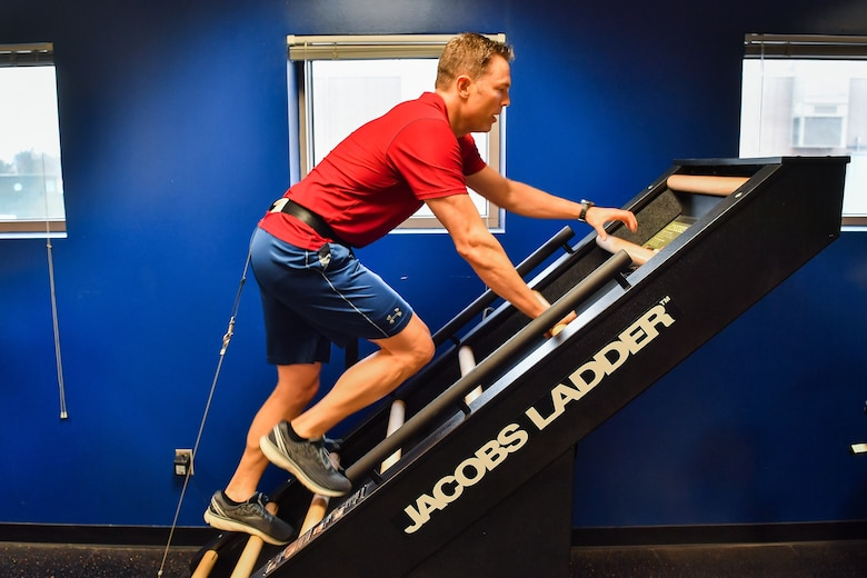 U.S. Air Force Capt. Wesley Althaus, 50th Operations Group Standardization and Evaluation Flight, climbs an exercise machine during the Heart Health Fair at Schriever Air Force Base, Colorado, March 26, 2019. The machine is designed to create a high intensity, low-impact exercise. (U.S. Air Force photo by Kathryn Calvert)