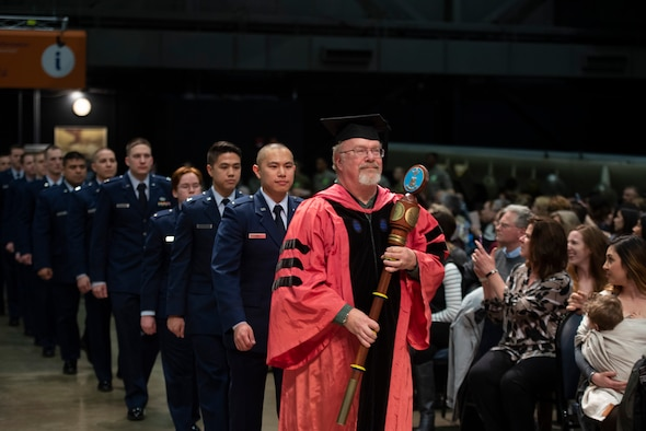 Dr. William Wiesel, grand marshal, leads 2nd Lt. Kevin Lin, the other graduates and faculty into the Air Force Institute of Technology commencement ceremony March 21, 2019, at the National Museum of the U.S. Air Force, Wright-Patterson Air Force Base, Ohio. More than 200 advanced degrees were awarded to officers, enlisted and civilians from the U.S., Australian and Brazilian armed forces. (U.S. Air Force photo by R.J. Oriez)