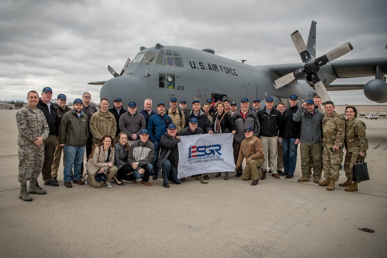 """More than two-dozen civilian employers stand in front of a Kentucky Air National Guard C-130 Hercules aircraft at Wright-Patterson Air Force Base, Ohio, March 15, 2019, with Airmen from the 123rd Airlift Wing and representatives of the Kentucky Committee for Employer Support of the Guard and Reserve The employers were participating in an ESGR """"Bosslift,"""" which enhances awareness and understanding between National Guardsmen and the civilian employers for whom they work when they're not on duty. (U.S. Air National Guard photo by Staff Sgt. Joshua Horton)"""