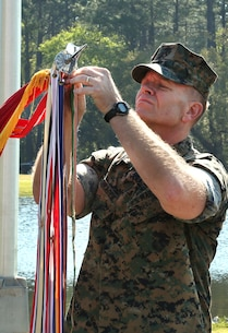 Brig. Gen. Joseph F. Shrader, commanding general, Marine Corps Logistics Command, attaches the Meritorious Unit Commendation with bronze star in lieu of fourth award to the organizational colors during a ceremony held at Covella Pond aboard Marine Corps Logistics Base Albany, March 21.