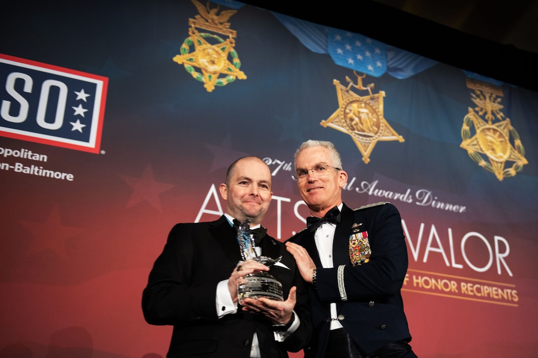 Air Force Gen. Paul J. Selva, vice chairman of the Joint Chiefs of Staff, stands next to a man holding an award