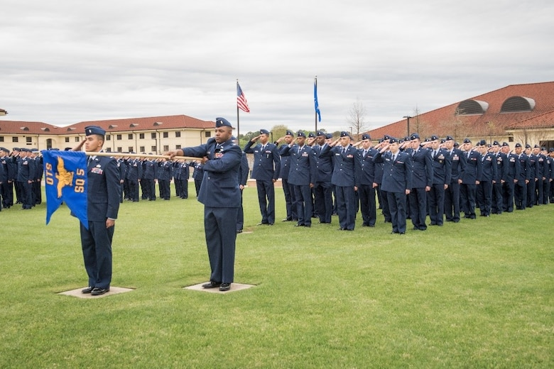 Air Force Officer Training School officer trainees salute during the ceremonial playing of 'Ruffles and Flourishes,' March 15, 2019, Maxwell Air Force Base, Alabama. This graduating class of officers is the largest ever and one of the first under the new consolidated OTS training program. (U.S. Air Force photo by Airman First Class Matthew Markivee)