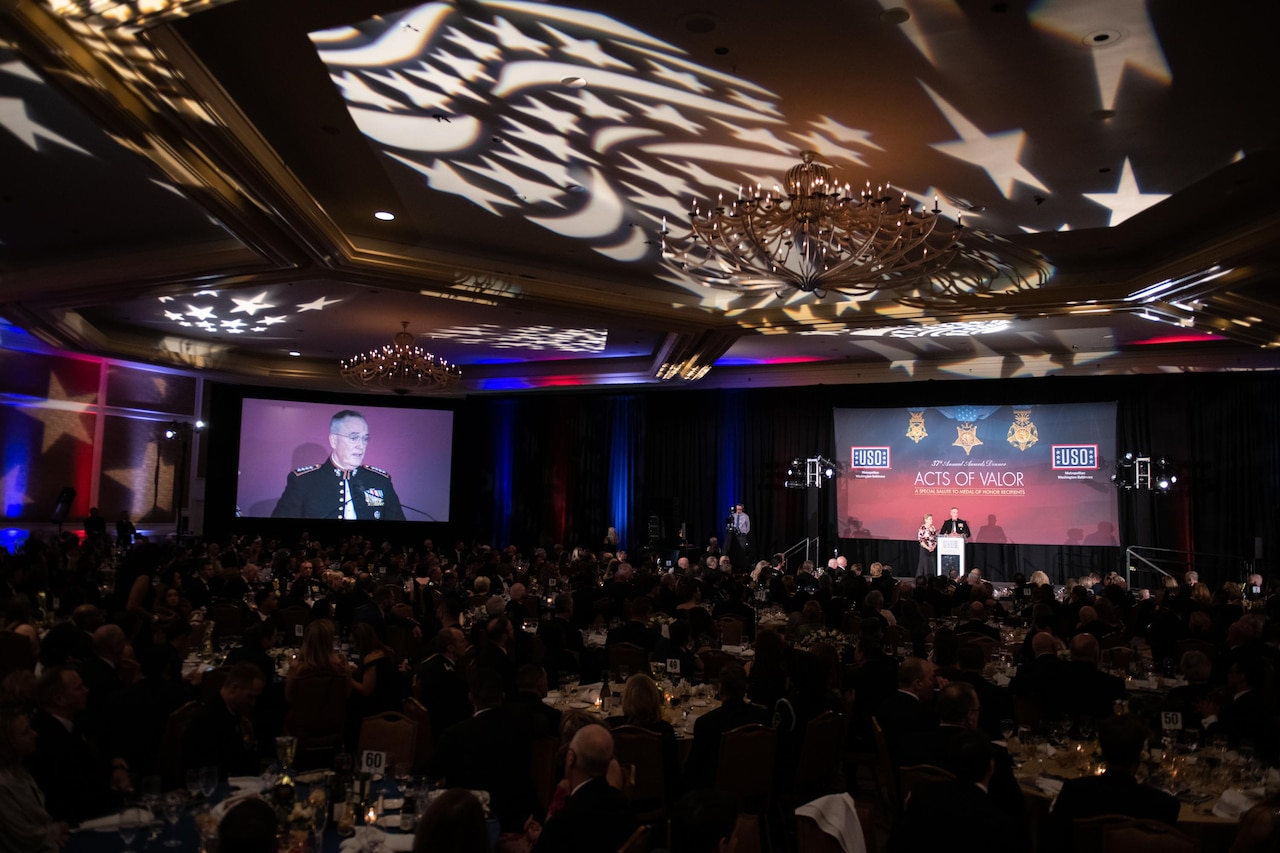 Large screen in banquet hall shows Joint Chiefs chairman speaking from a lectern
