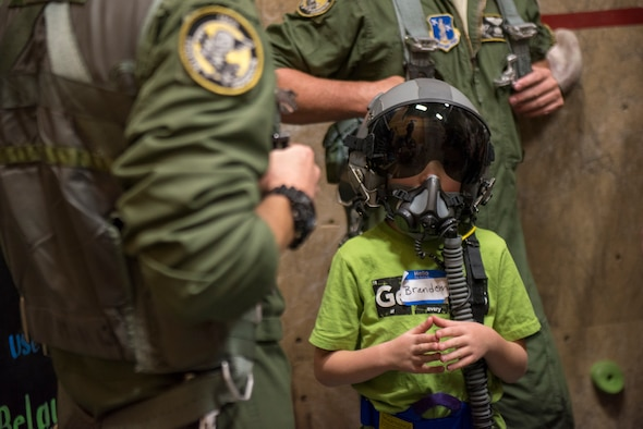 A child wears a helmet belonging to a fighter pilot from the 190th Fighter Squadron during the Courageous Kids Climbing event at the YMCA, Boise, Idaho, Sept. 9, 2018.