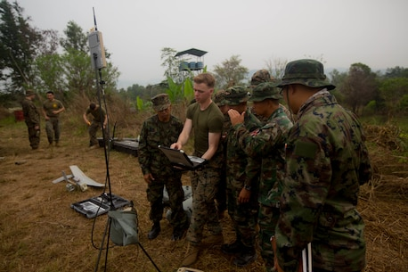 U.S. Marine Cpl. Kyle Bougeno with 3rd Battalion, 3rd Marine Regiment, explains the use of a laptop and its various video feed capabilities to Royal Thai counterparts at Camp Ban Chan Khrem, the Kingdom of Thailand, Feb. 19, 2018.