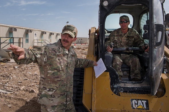 Master Sgt. Christopher Beckett, left, 379th Expeditionary Civil Engineer Squadron (ECES) heavy equipment section chief, and Tech. Sgt. John Beckett, right, 379th ECES heavy equipment project lead, work together at a construction site March 27, 2019, at Al Udeid Air Base, Qatar. The brothers, who have served in the Arizona Air National Guard since 2003, are currently deployed together to the same ECES unit at Al Udeid Air Base. (U.S. Air Force photo by Tech. Sgt. Christopher Hubenthal)