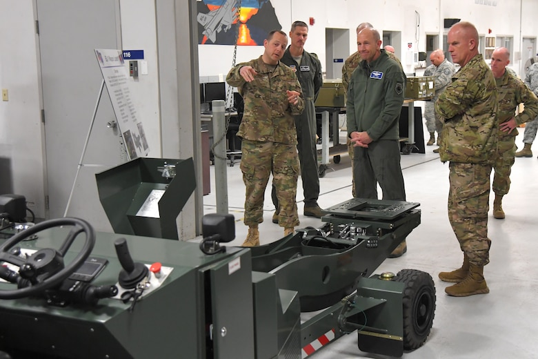 U.S. Air Force Gen. Mike Holmes, commander of Air Combat Command, center, and Command Chief Master Sgt. Frank Batten, right, are briefed about the BL-1 weapons loader by U.S. Air Force Master Sgt. Ryan Hanner, 388th Maintenance Group, during a visit to the 388th Fighter Wing March 26, 2019, at Hill Air Force Base, Utah. (U.S. Air Force photo by Todd Cromar)