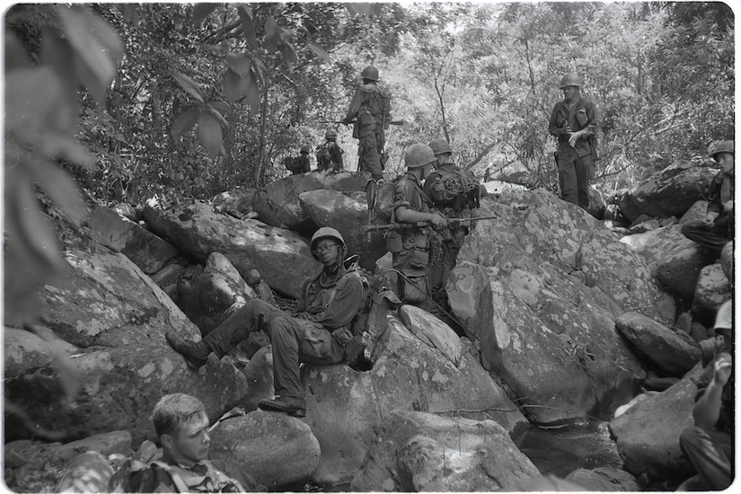 Marines relax on rocks in the Vietnamese jungle.