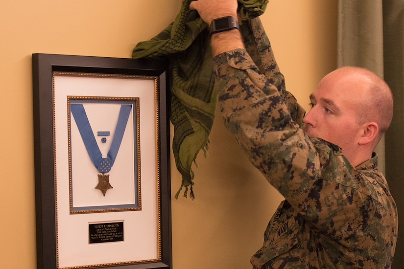 A Marine unveils a plaque on a wall that holds the Medal of Honor.