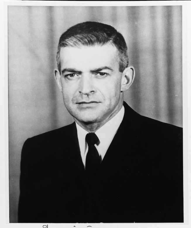 A headshot of a man in suit and tie.