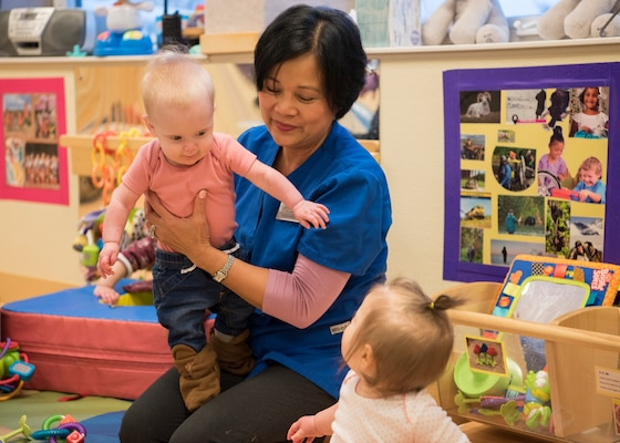 Nelia McKeown, a Sitka Child Development Center child and youth program assistant, holds a child during playtime at Joint Base Elmendorf-Richardson, Alaska, Dec. 14, 2018. Childcare will not be cut in the Army's FY20 budget request, senior leaders testified to the Senate Appropriations Committee, Defense subcommittee, March 27, 2019. In fact, they said a number of initiatives to boost childcare are planned.