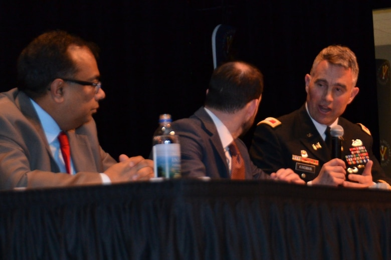 Three men sitting on a discussion panel at table