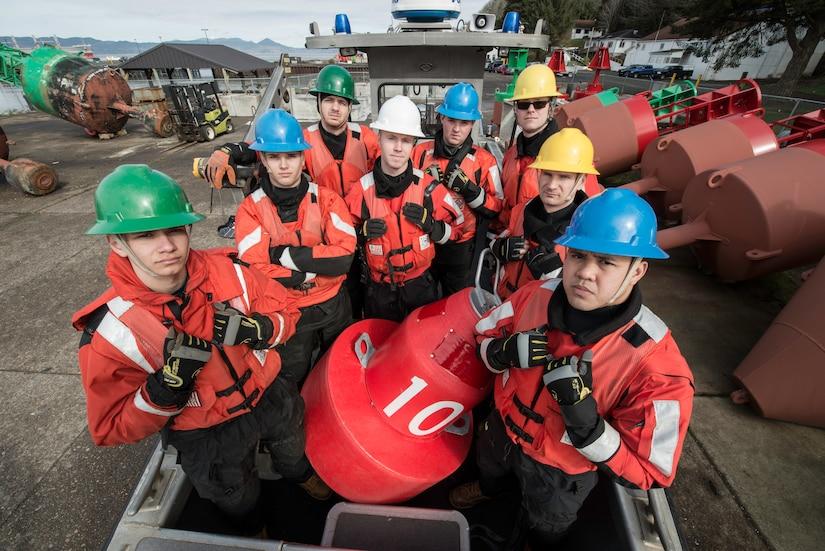 Eight Coast Guardsmen pose with an orange buoy.